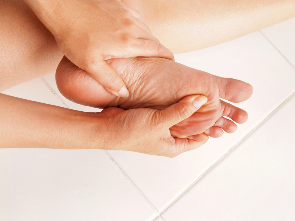 woman holding foot because of neuropathy pain