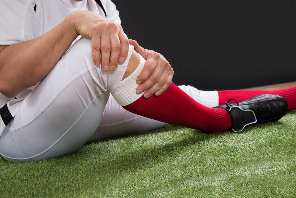football player holding knee in pain from a sports injury