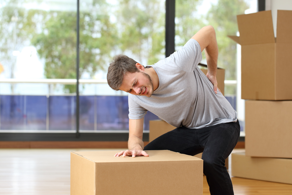 professional mover holding his back in pain from a work injury